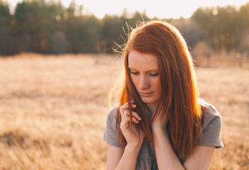 Beauty Young Woman with Red Hair in Golden Field at Sunset.