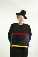 Thanksgiving pilgrim holding chalkboard.