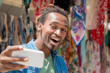 happy guy smiling and taking selfie with mobile phone
