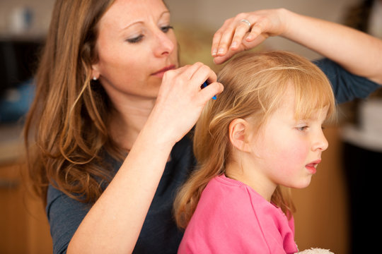 Mother combs hair to a little girl