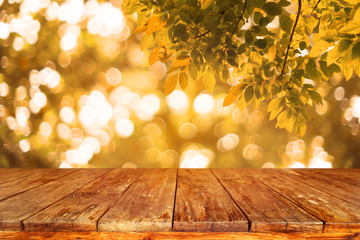 Top of wood table with autumn abstract background. light bokeh from tree in fall - Empty ready for your product display or montage. vintage color tone