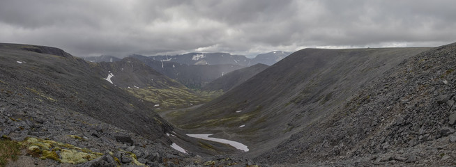 Panorama of mountain valley with mosses and rocks covered with lichens. Cloudy sky before storm.  Khibiny mountains above the Arctic circle, Kola peninsula, Russia