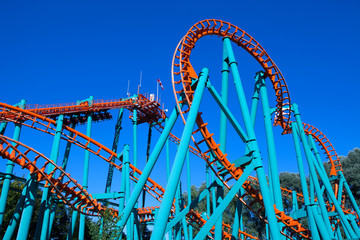 Orange rollercoaster with blue sky in the background