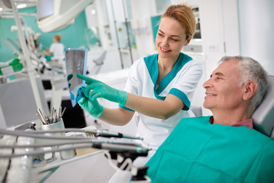 Dentist showing teeth problem on dental X-ray .