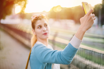 Woman taking selfie in park at sunset