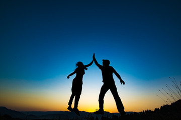 Girl and man holding for hands and jumping. They are successfull people.