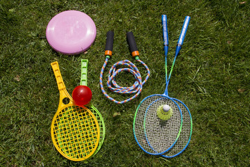 Group of sports equipment including tennis rackets, badminton rackets, skipping rope and frisbee on green grass field