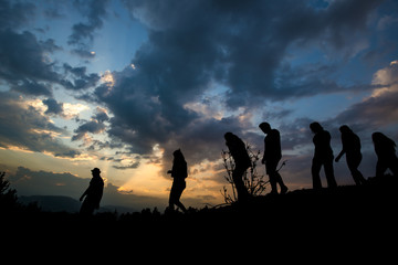 group of friends are walking in the nature sunset