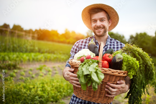 Man holding basket with organic vegetables