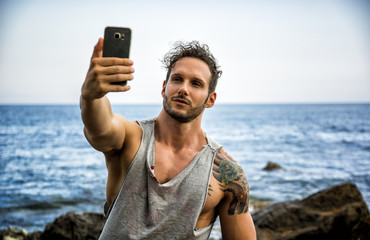 Athletic man at the seaside using cell phone to take selfie photo with the sea behind him