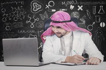 Arabian doctor looking at laptop in laboratory