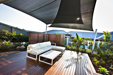 Outdoor patio area with white benches and wooden floor