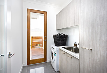 Modern laundry room with grey cupboards on the wall