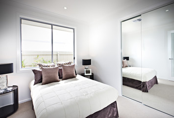 Classic bedroom with windows and lamps beside a mirror