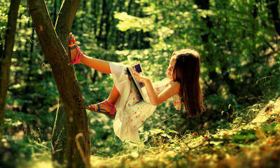 Paranormal activity. Girl floating in the forest and enjoy the summer day, reading the book