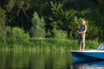 Mature man on a motor boat. Fishing.