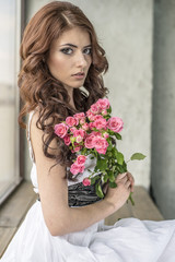 Haired girl in a wedding dress and makeup with a festive with a bouquet of roses