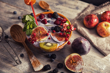 bright detox smoothie with berries on wooden background bowl