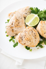 Chicken breasts with parsley and citrus on white background close up. Healthy food.