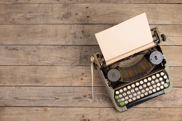 Vintage typewriter on the old wooden desk
