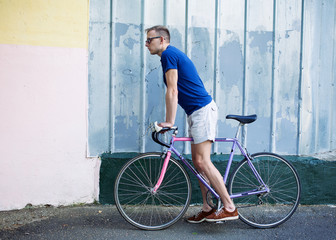 Young man going to ride a bike against the wall