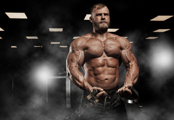 Muscular athletic bodybuilder fitness model posing after exercises in gym Wall mural