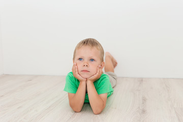 Little handsome boy with blue eyes lying on the floor