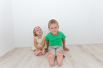 Beautiful boy and girl sitting on the floor