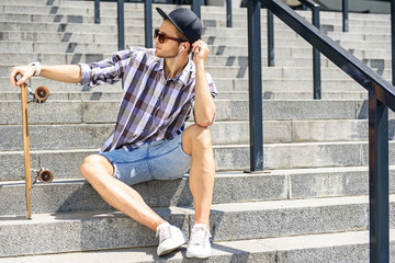 Cheerful guy with resting skateboard on steps
