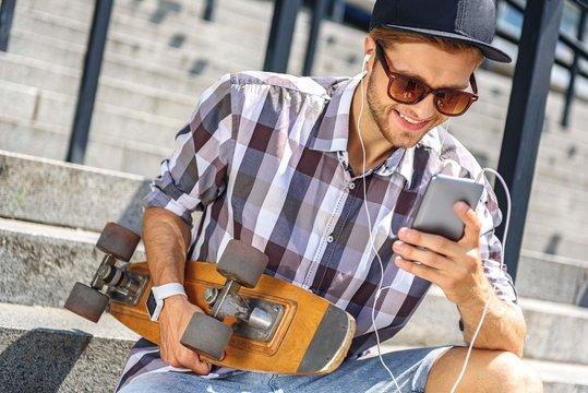 Joyful male skater using smartphone on steps