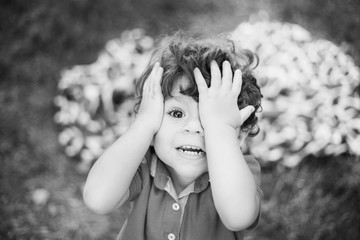 Black and white close up image of cute little toddler boy. Portrait of sad funny kid covering his eyes with hands. Child looking at camera. Horizontal monochrome photo.