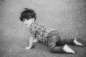 little cute toddler boy crawling outside. Caucasian child dressed in casual clothing: denim jeans, shirt and sneakers. Portrait of kid with beautiful dark curly hair. Horizontal black and white image.