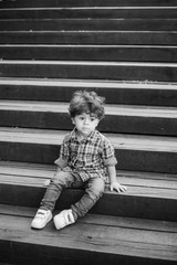 Portrait of little cute child sitting on wood stairs in city park. Model released pensive caucasian boy looks at camera through wooden parapet of stairs. Vertical and white  photography