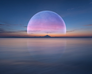 Pink planet like moon above the ocean and mountain