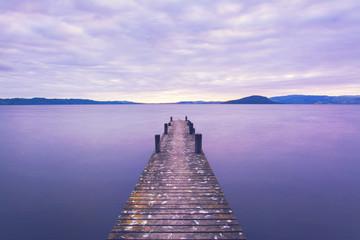 Romantic sunrise scene at a pier looking out upon Lake Rotorua, New Zealand