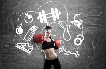 Woman boxer near blackboard with sport icons