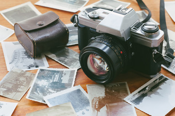 Film camera that had been popular in the past on a wooden table covered with photographs