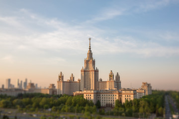 Soften edge view of sunset Moscow university framed with green trees under cloudy sky