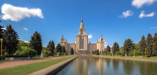 Soften edge sunny view of Moscow university under blue cloudy sky in summer with water reflections