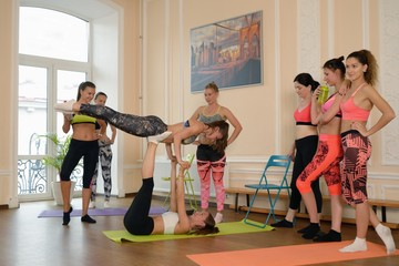 Group of young girl does acrobatic exercise