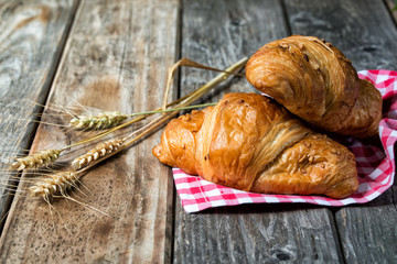 Two croissants with nuts on textile and spikelets, wooden background