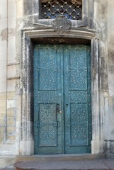 Old blue metal forged door in a stone building