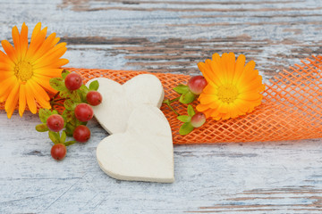 Flower, berries and wooden heart lying on wood