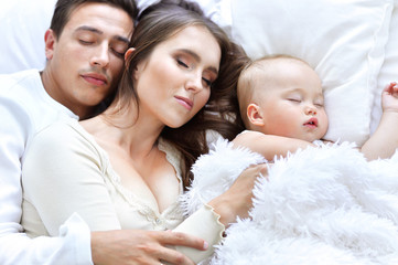 Sleeping family and child in bed