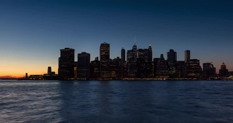 Fotomurales - Time lapse cityscape view of the New York City Financial District and East River with passing boats. Lower Manhattan skyscrapers between sunset and dusk with city lights