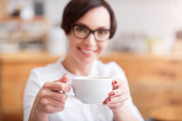 Attractive businesswoman holding cup