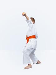 In rack of karate karateka boy beats punch arm