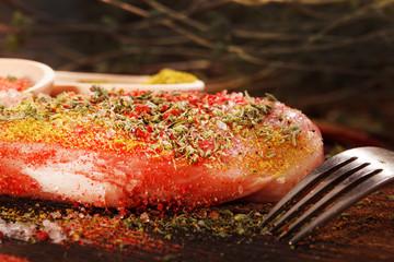 Raw juicy meat steak on dark wooden background