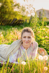 Middle-aged cheerful blond woman laying outdoors on meadow