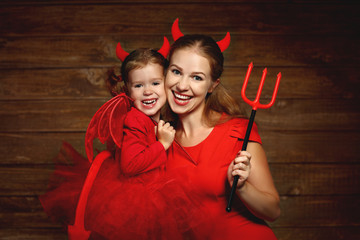 Family mother and child daughter celebrate Halloween in devil co